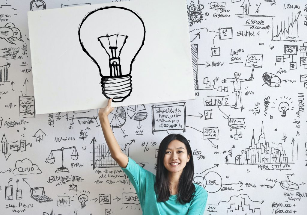 Woman holding up a large drawing of a light bulb